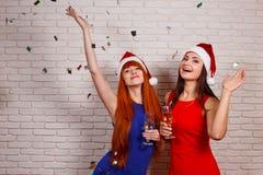Deux belles femmes heureuses dansant, ayant l'amusement et buvant le champion Image stock