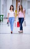 Deux belles femmes marchant dans le mail avec des paniers Image stock