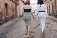 Deux belles femmes marchant sur la rue faisant le discours de mains Photo libre de droits
