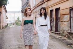 Deux belles femmes marchant sur la rue faisant le discours de mains Images stock