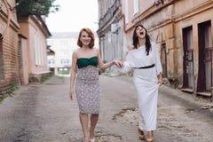 Deux belles femmes marchant sur la rue faisant le discours de mains Image libre de droits