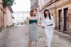 Deux belles femmes marchant sur la rue faisant le discours de mains Images libres de droits