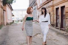 Deux belles femmes marchant sur la rue faisant le discours de mains Photographie stock libre de droits