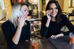 Deux belles femmes parlant au téléphone en café Photo stock