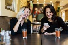 Deux belles femmes parlant au téléphone en café Images libres de droits