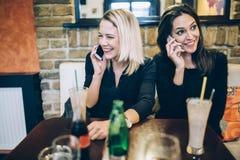 Deux belles femmes parlant au téléphone en café Photo libre de droits