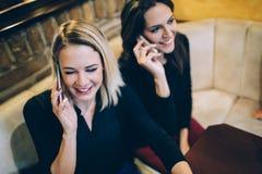 Deux belles femmes parlant au téléphone en café Photos libres de droits