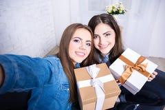Deux belles femmes prenant la photo de selfie avec des présents dans la vie Image stock