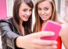 Deux belles femmes prenant un selfie au téléphone portable Image libre de droits