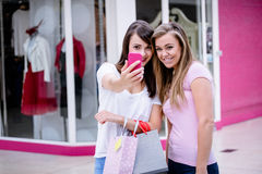 Deux belles femmes prenant un selfie dans le centre commercial Photographie stock
