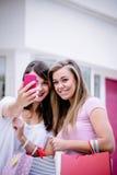 Deux belles femmes prenant un selfie dans le centre commercial Images stock