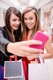 Deux belles femmes prenant un selfie dans le centre commercial Photos stock