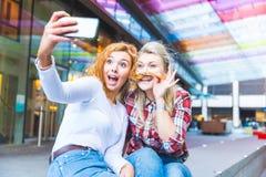 Deux belles femmes prenant un selfie drôle Photos stock