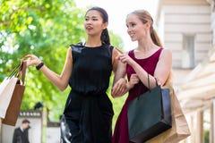 Deux belles femmes recherchant des boutiques de mode pendant les achats Photos stock