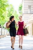 Deux belles femmes recherchant des boutiques de mode pendant les achats Images stock