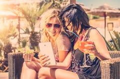 Deux belles femmes regardant le téléphone Image stock
