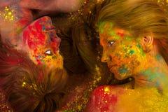 Deux belles femmes se trouvant sur le plancher dans les couleurs de Holi Photographie stock