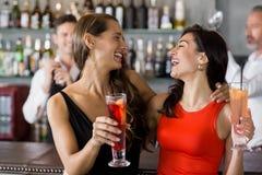 Deux belles femmes tenant le verre de cocktail Photographie stock libre de droits