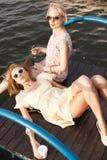 Deux belles filles à la jetée de mer Photographie stock libre de droits