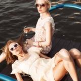 Deux belles filles à la jetée de mer Photo stock