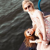 Deux belles filles à la jetée de mer Images libres de droits