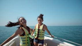 Deux belles filles appréciant un voyage sur une danse de bateau Photo libre de droits