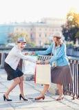 Deux belles filles avec des paniers ayant le combat dans la ville Image libre de droits