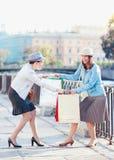 Deux belles filles avec des paniers ayant le combat dans la ville Photos libres de droits