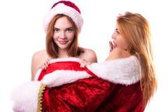 Deux belles filles avec les cheveux rouges dans les mitaines et le chapeau de Santa Claus photo libre de droits