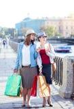Deux belles filles avec les paniers et la tasse de café Photographie stock libre de droits