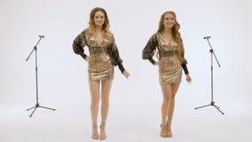 Deux belles filles chantent et dansent dans le studio, sur un fond blanc Tir d'une vidéo musicale banque de vidéos