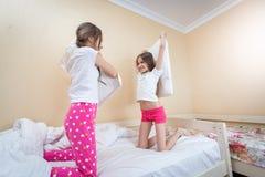Deux belles filles combattant avec des oreillers sur le lit à la chambre à coucher Photo libre de droits