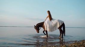 Deux belles filles dans de longues robes blanches ? cheval Les cavaliers de cheval fl?nent par l'eau le long de la c?te au couche clips vidéos