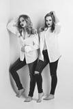 Deux belles filles dans des chemises et des jeans des hommes Photographie stock libre de droits
