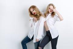 Deux belles filles dans des chemises et des jeans des hommes Images libres de droits