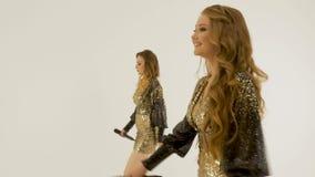 Deux belles filles dans des robes brillantes dansant et chantant dans le studio sur un fond blanc clips vidéos