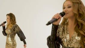 Deux belles filles dans des robes brillantes dansant et chantant dans le studio sur un fond blanc banque de vidéos