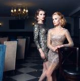 Deux belles filles dans des robes brillantes près de la barre Photo stock