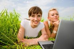 Deux belles filles dans l'amusement blanc travaillant sur l'ordinateur portatif Photos libres de droits