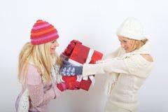 Deux belles filles de l'hiver avec des cadeaux de Noël Photographie stock libre de droits