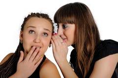 Deux belles filles de sourire partageant un secret Image libre de droits