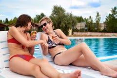 Deux belles filles en champagne potable de bikini Image stock