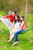 Deux belles filles et un jeune homme dans l'hamac Photo libre de droits