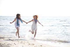 Deux belles filles exécutant sur la plage. Photographie stock libre de droits
