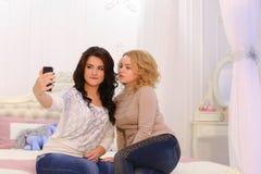 Deux belles filles font la photo de selfie, utilisant l'instrument, pour la mémoire, Images libres de droits