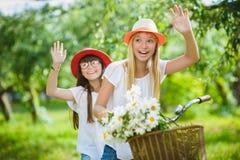 Deux belles filles heureuses de hippie riant et posant pour l'appareil-photo avec des vélos Photographie stock libre de droits