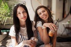Deux belles filles minces de sourire jeunes avec de longs cheveux foncés, vêtements sport de port, s'asseyent l'un à côté de l'au photographie stock libre de droits
