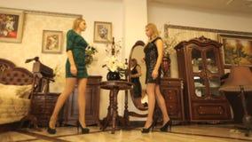 Deux belles filles modernes sur le fond d'une salle chic avec les meubles chers banque de vidéos