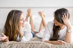 Deux belles filles parlant et souriant tout en se trouvant sur un lit Photographie stock