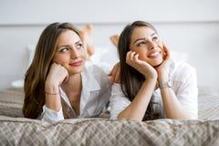 Deux belles filles parlant et souriant tout en se trouvant sur un lit Photographie stock libre de droits